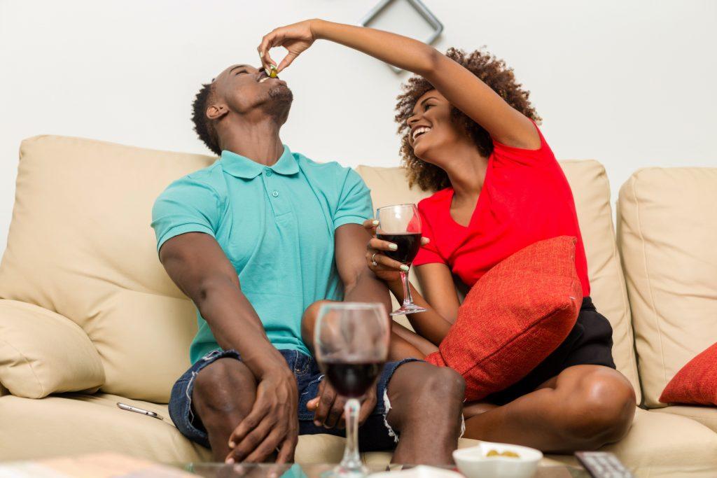 Couple feeding each other on sofa